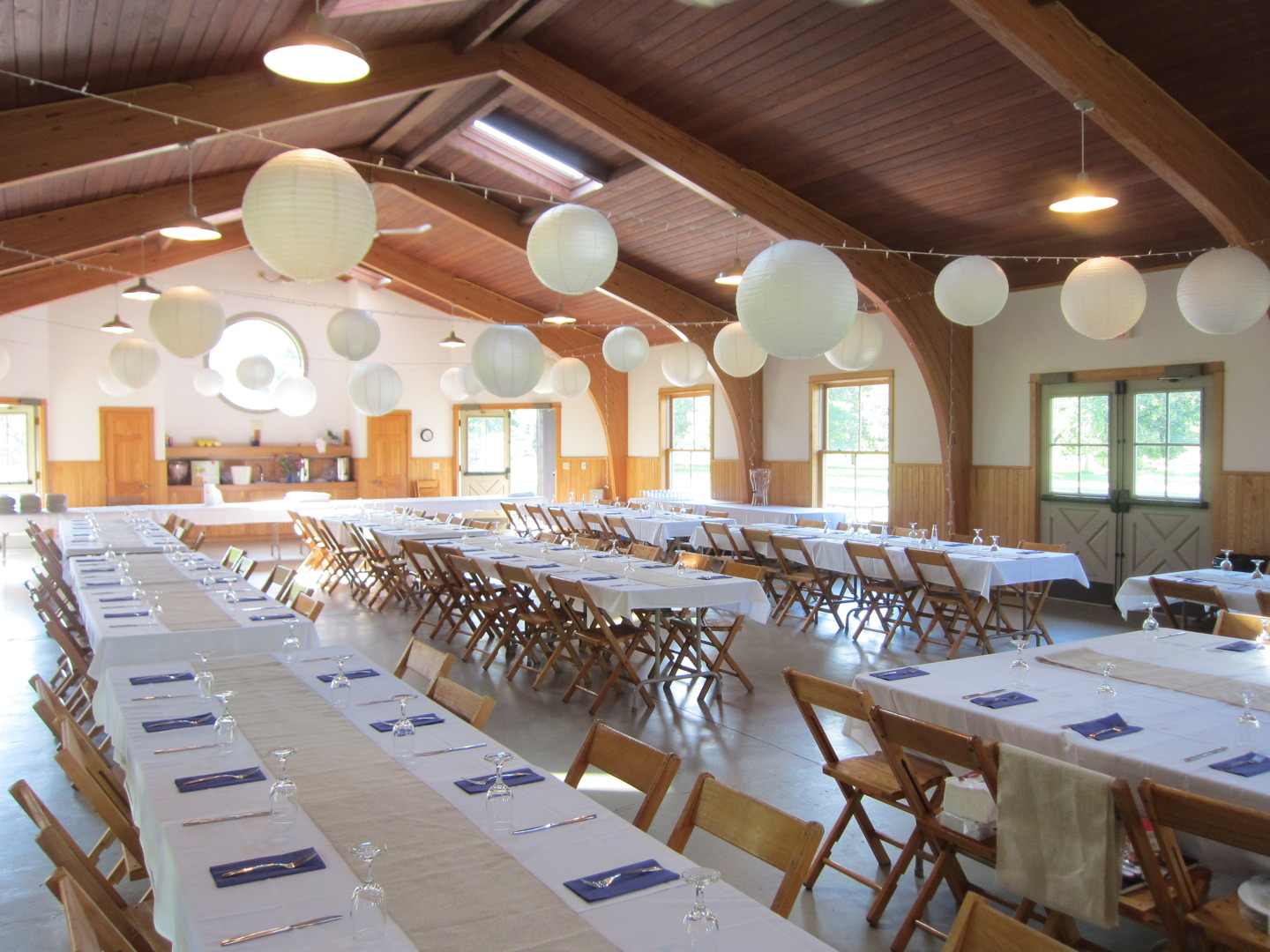 We installed all white christmas lights and hung white paper lanterns for inexpensive,easy yet impactful ceiling decor. Burlap runners and purple coneflowers.